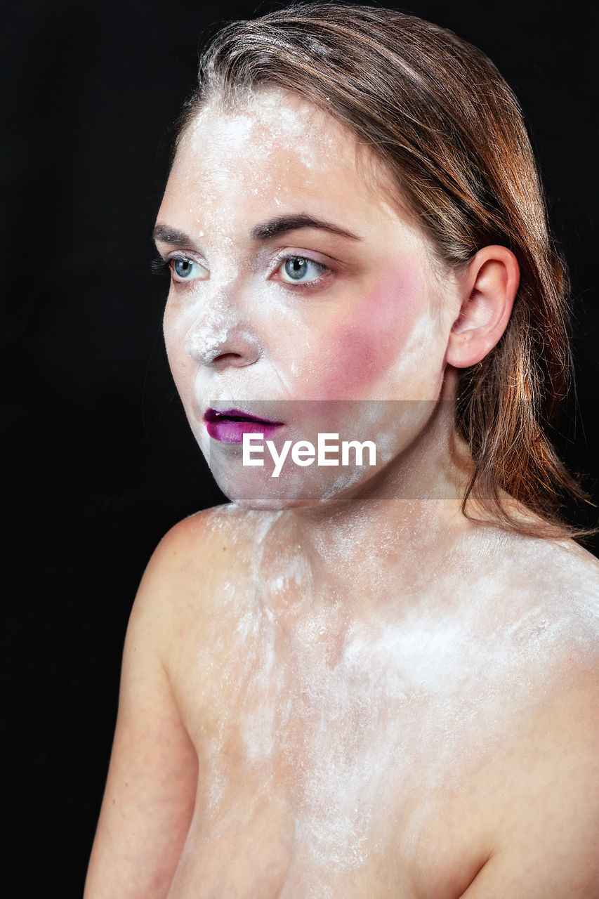 Close-up of shirtless woman with make-up and talcum powder against black background