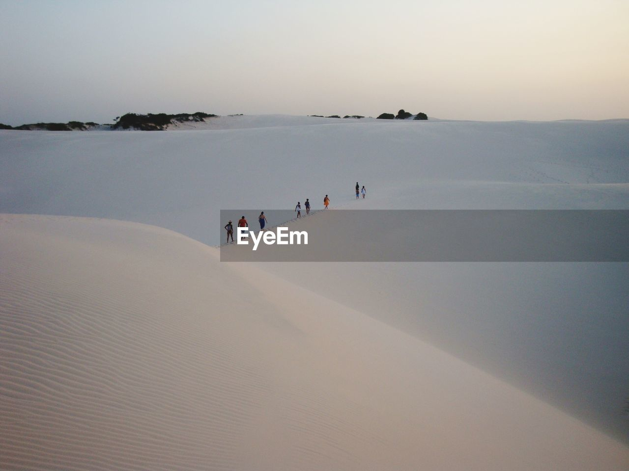 People walking on sand dune against sky during sunset