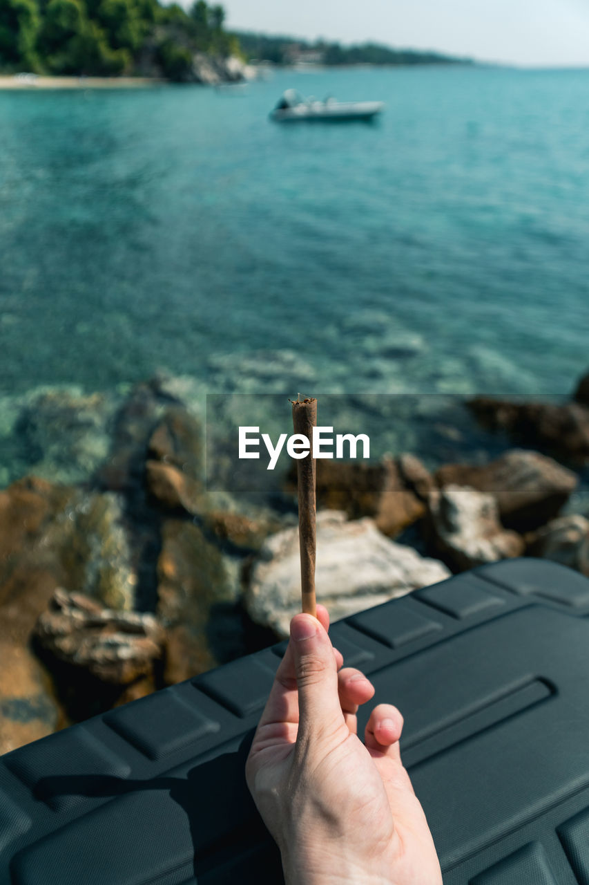 human hand, hand, human body part, water, one person, real people, day, unrecognizable person, nature, focus on foreground, sea, human finger, holding, lifestyles, finger, leisure activity, body part, personal perspective, outdoors