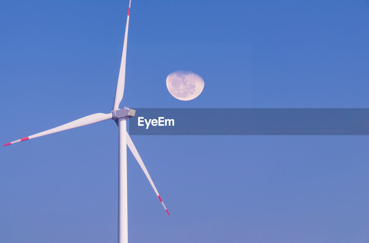 low angle view, sky, clear sky, turbine, blue, wind turbine, renewable energy, alternative energy, fuel and power generation, no people, nature, moon, wind power, environment, environmental conservation, copy space, technology, outdoors, beauty in nature, day, planetary moon, sustainable resources, power supply
