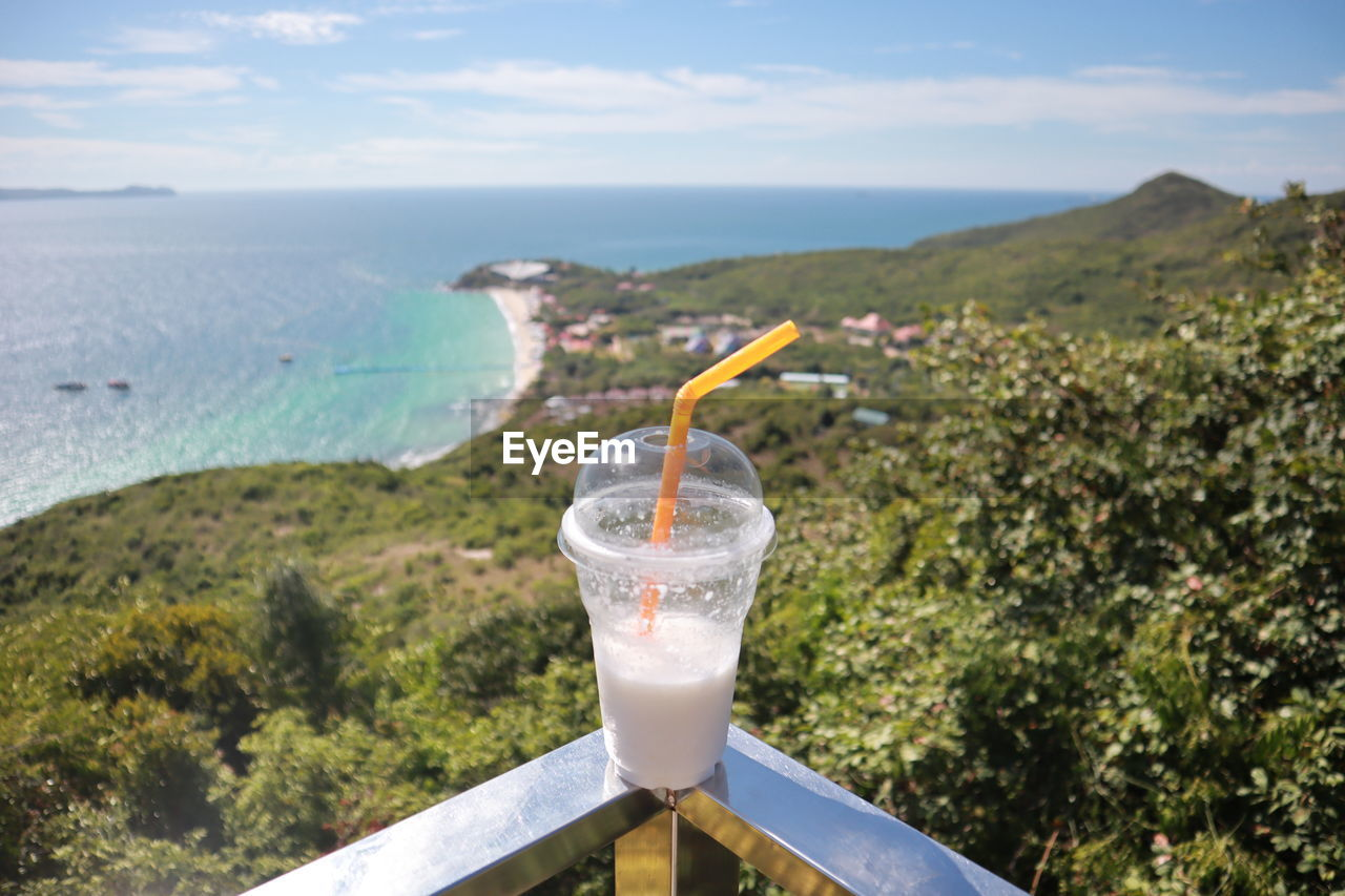 drink, refreshment, water, drinking straw, glass, sky, sea, straw, food and drink, nature, day, scenics - nature, drinking glass, focus on foreground, freshness, tranquility, beauty in nature, no people, tranquil scene, outdoors