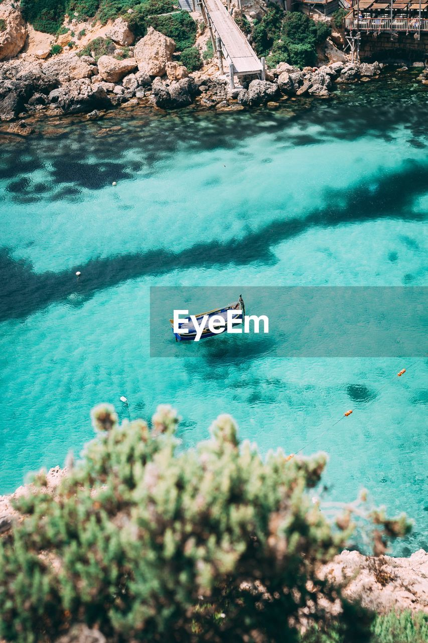 water, nautical vessel, transportation, mode of transportation, sea, nature, high angle view, day, beauty in nature, turquoise colored, sunlight, travel, outdoors, rock, blue, beach, land, tranquility, scenics - nature
