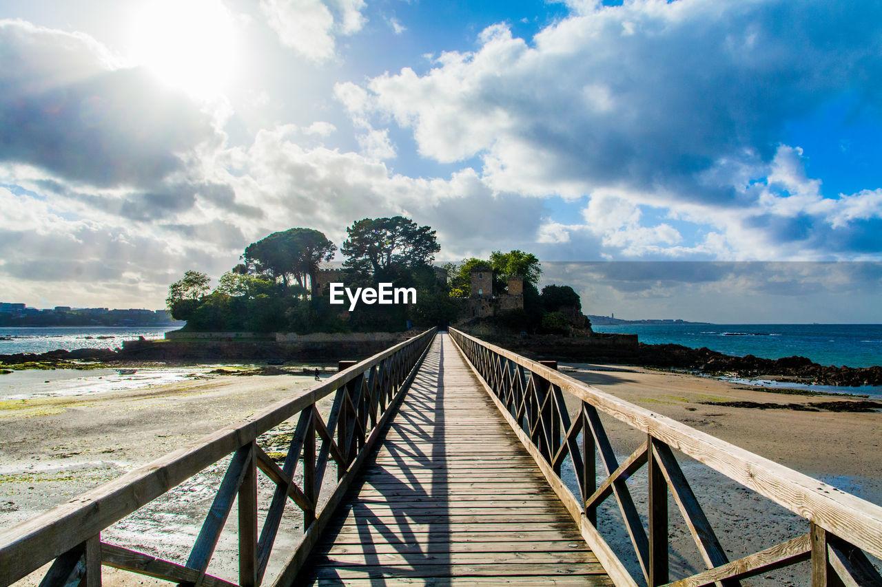 Footbridge leading towards castle on seaside