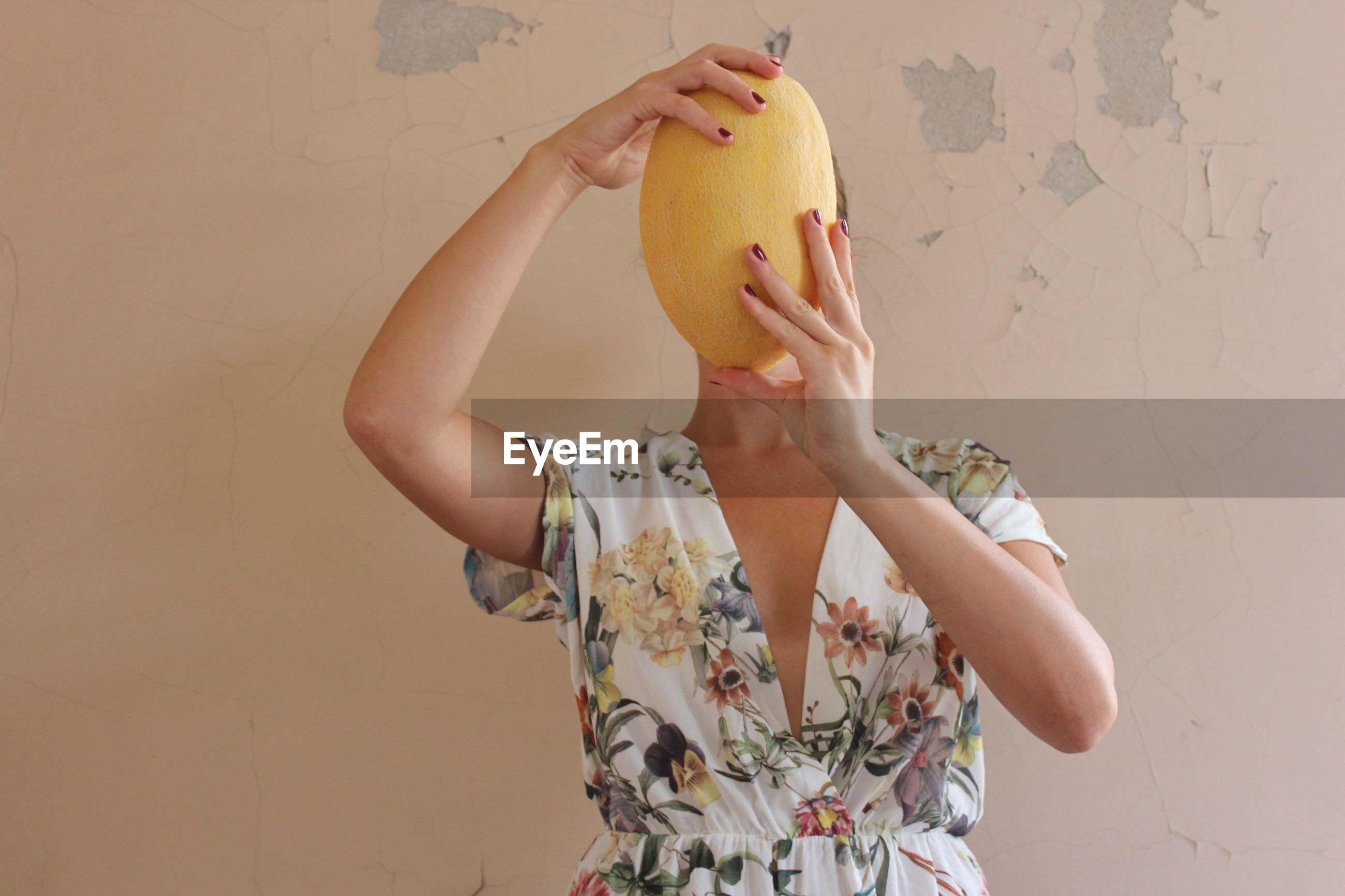 MIDSECTION OF WOMAN STANDING AGAINST ORANGE WALL