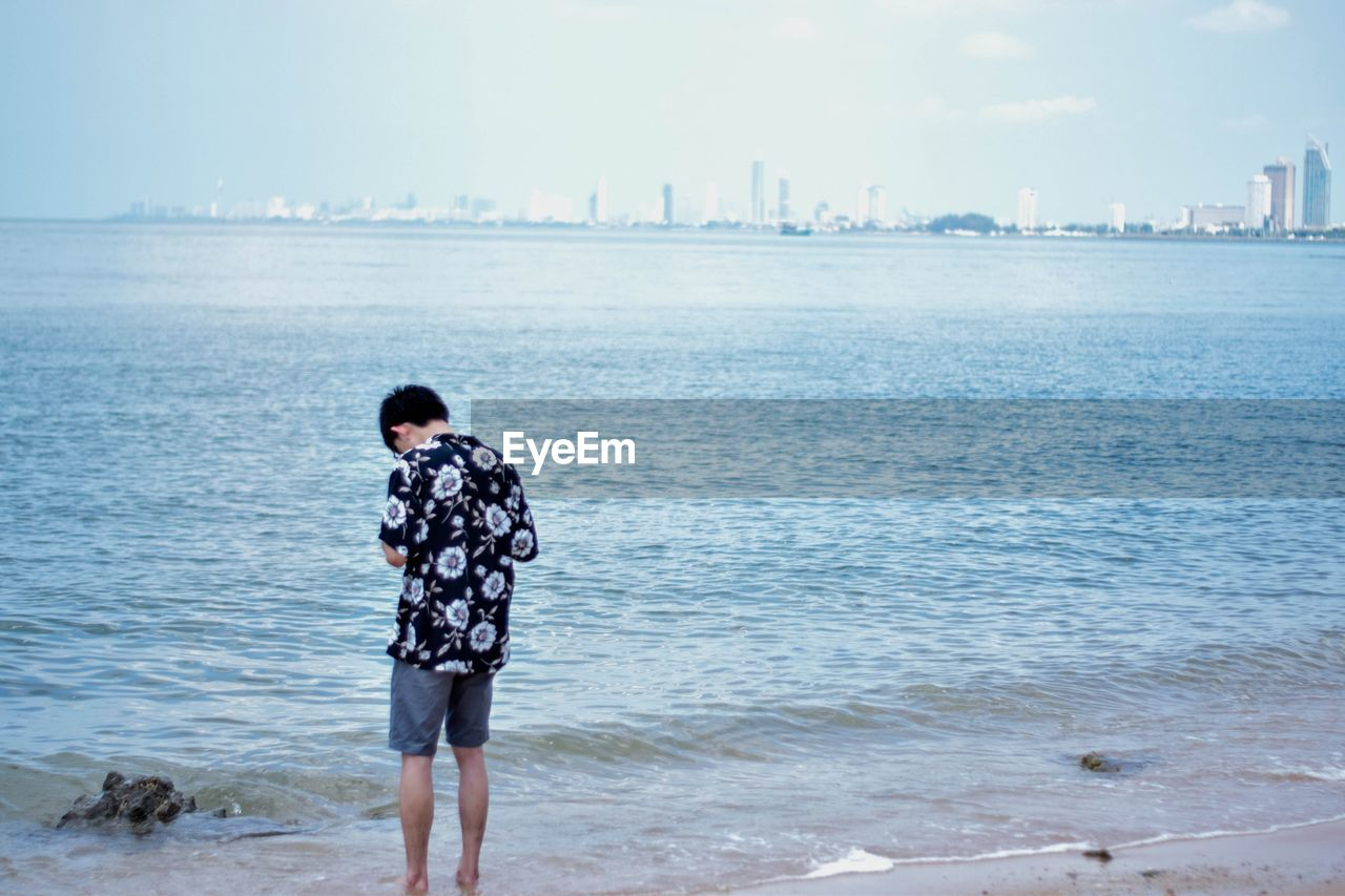 water, sea, beach, land, real people, one person, sky, leisure activity, nature, day, standing, rear view, casual clothing, three quarter length, lifestyles, beauty in nature, scenics - nature, holiday, outdoors, looking at view