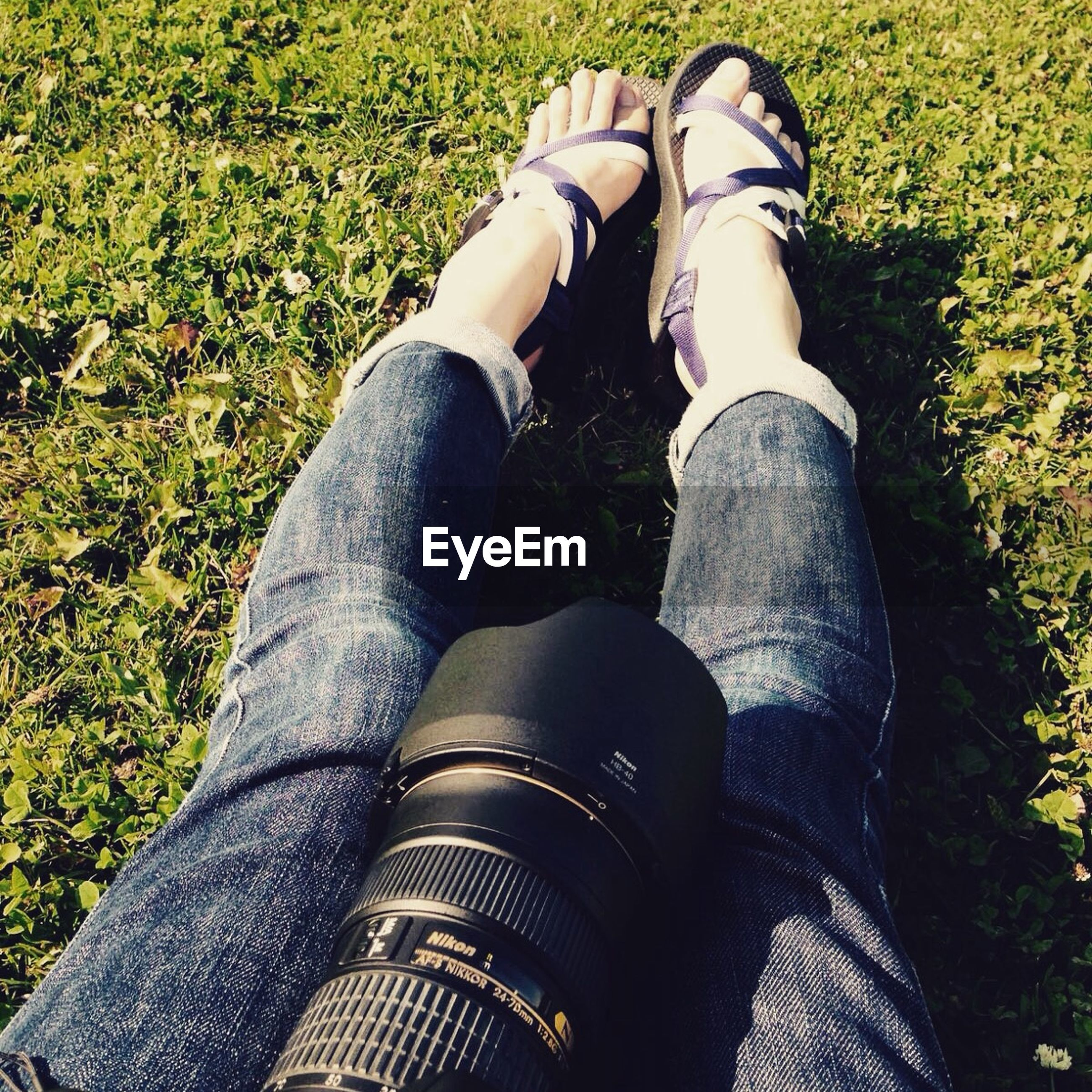 low section, person, shoe, personal perspective, jeans, lifestyles, grass, human foot, leisure activity, high angle view, footwear, relaxation, casual clothing, field, standing, sitting, legs crossed at ankle