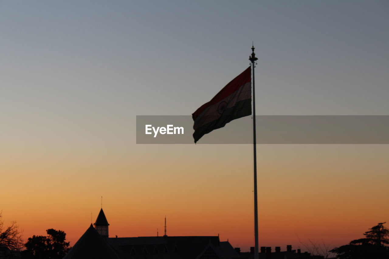 LOW ANGLE VIEW OF SILHOUETTE FLAG AGAINST SKY DURING SUNSET