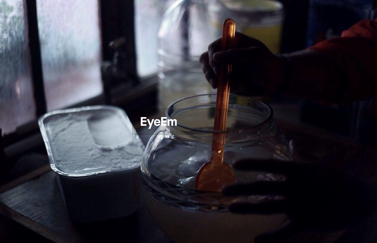 Man's hands stirring liquid in glass bowl