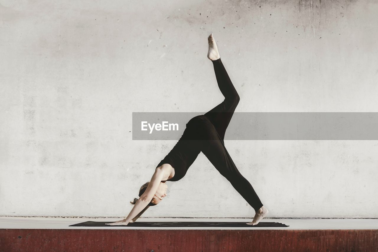 Side View Of Woman Exercising Against Wall