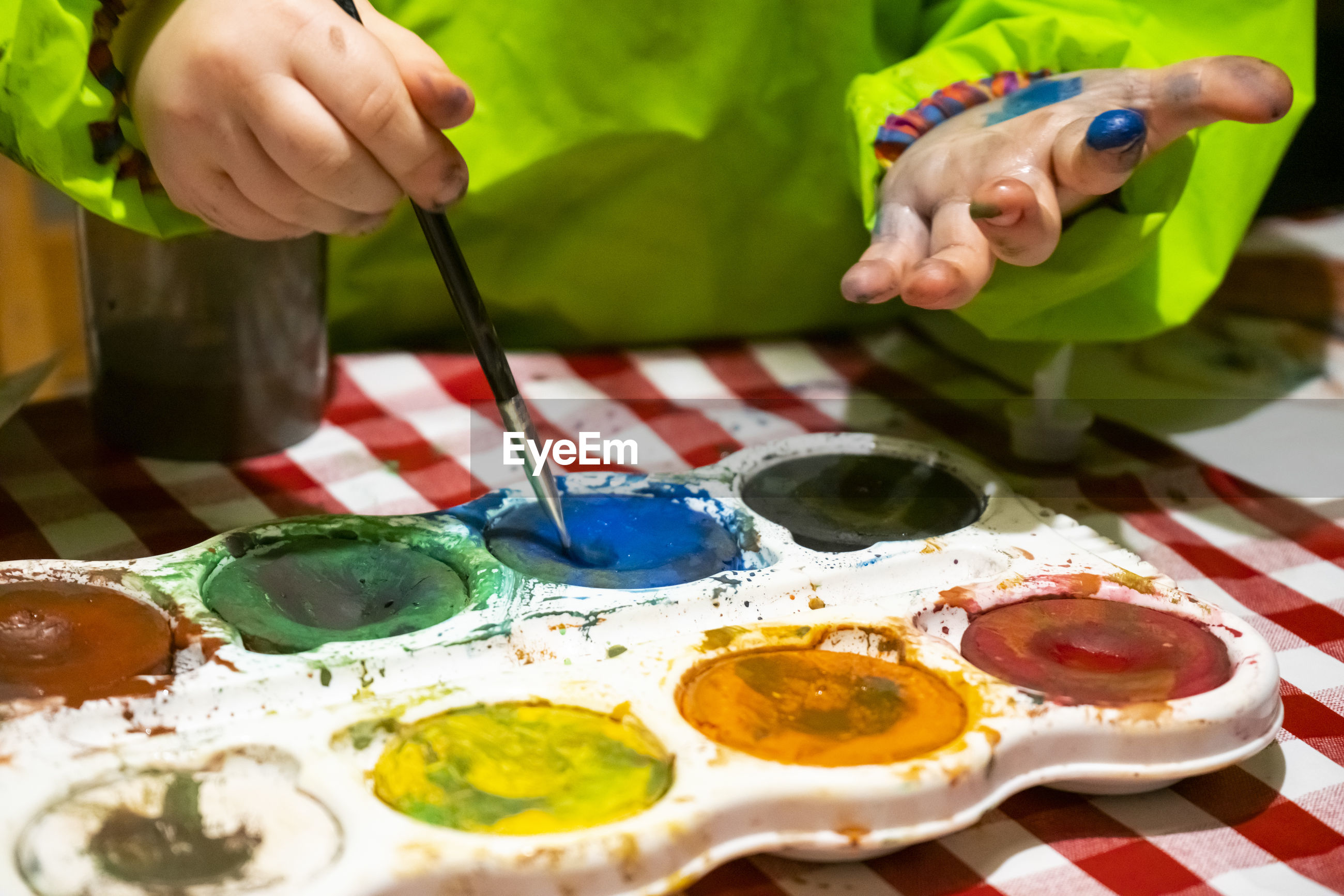 Midsection of girl holding paintbrush in paints on table