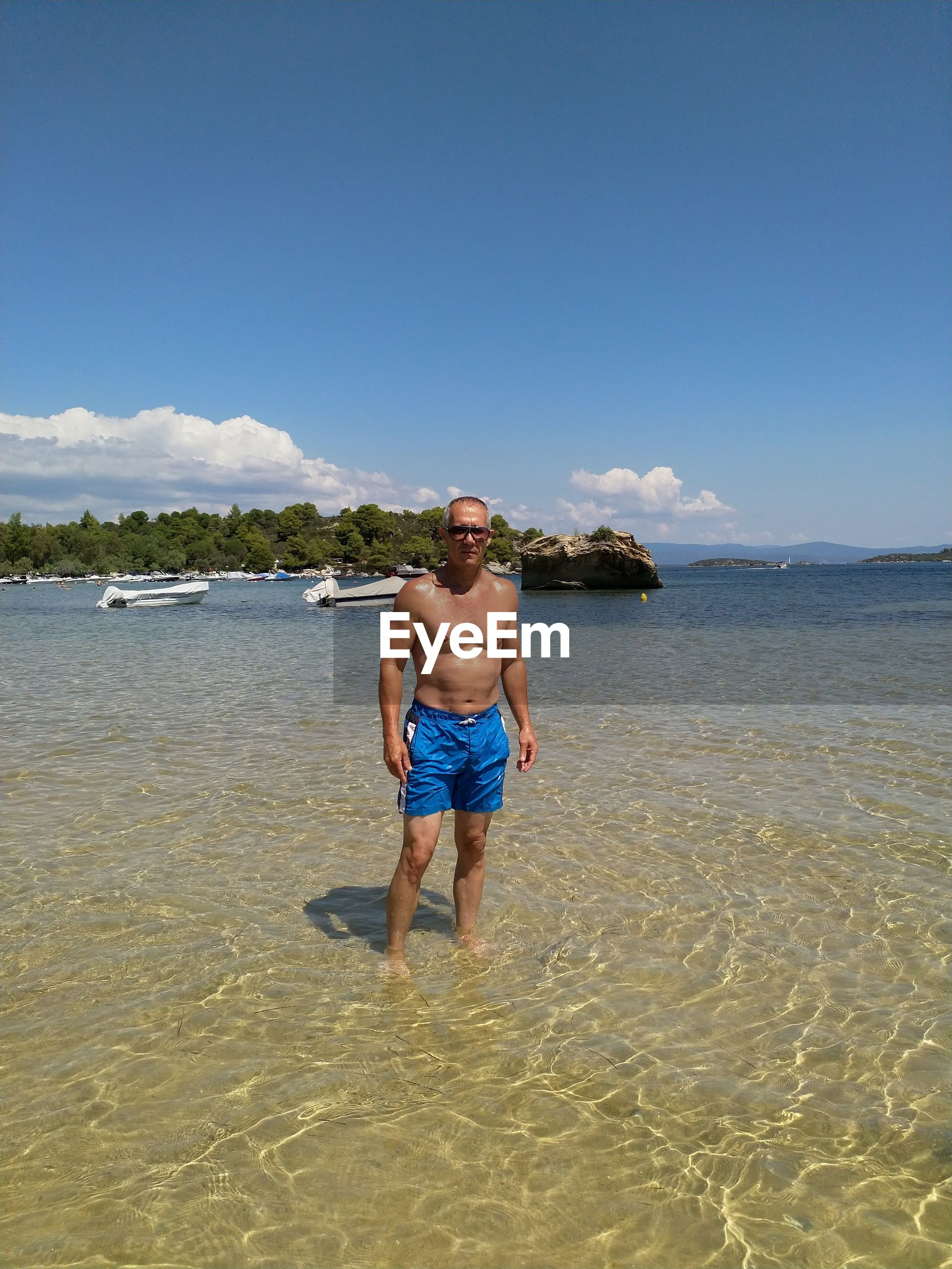 one person, beach, sky, water, shirtless, sea, leisure activity, land, real people, full length, nature, lifestyles, beauty in nature, day, vacations, men, trip, holiday, shorts, outdoors, mature men