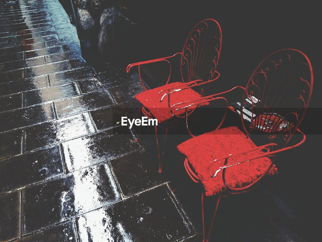 High Angle View Of Red Chairs On Wet Sidewalk