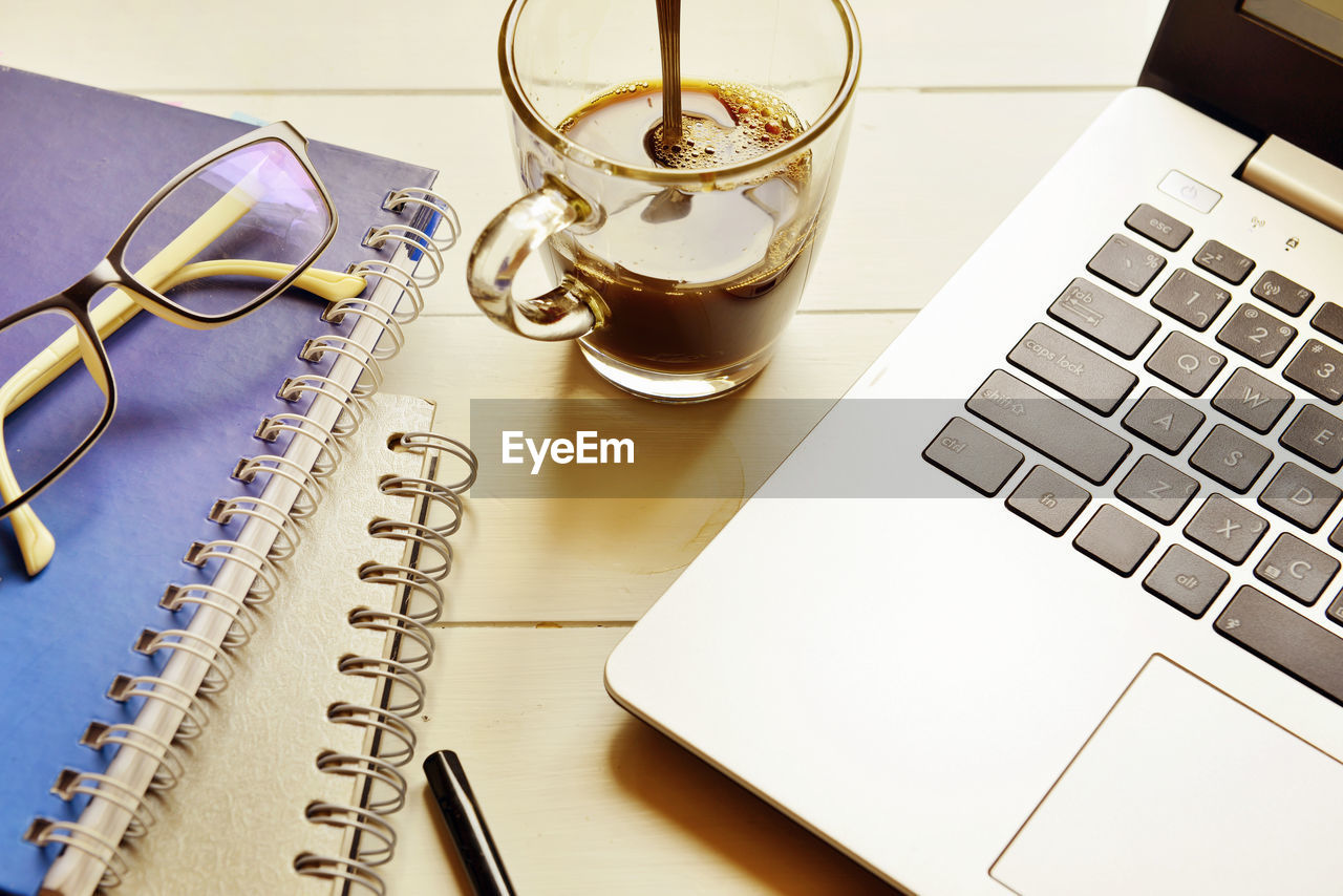 Laptop With Black Coffee And Spectacles On Spiral Diary Kept On Wooden Table
