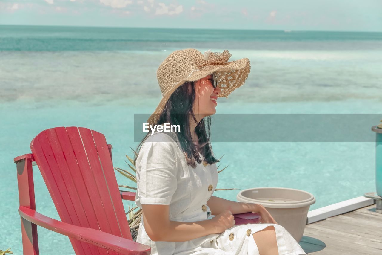 Smiling woman sitting on chair at beach