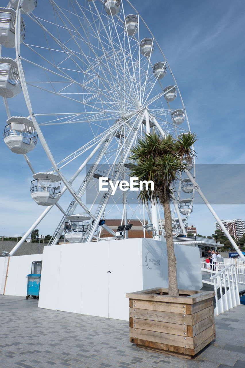 LOW ANGLE VIEW OF FERRIS WHEEL ON BEACH