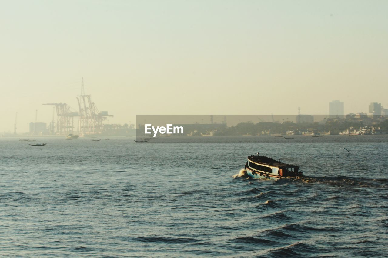 nautical vessel, water, transportation, sky, mode of transportation, waterfront, building exterior, architecture, sea, built structure, city, no people, nature, copy space, clear sky, building, day, cityscape, outdoors, passenger craft, office building exterior, skyscraper