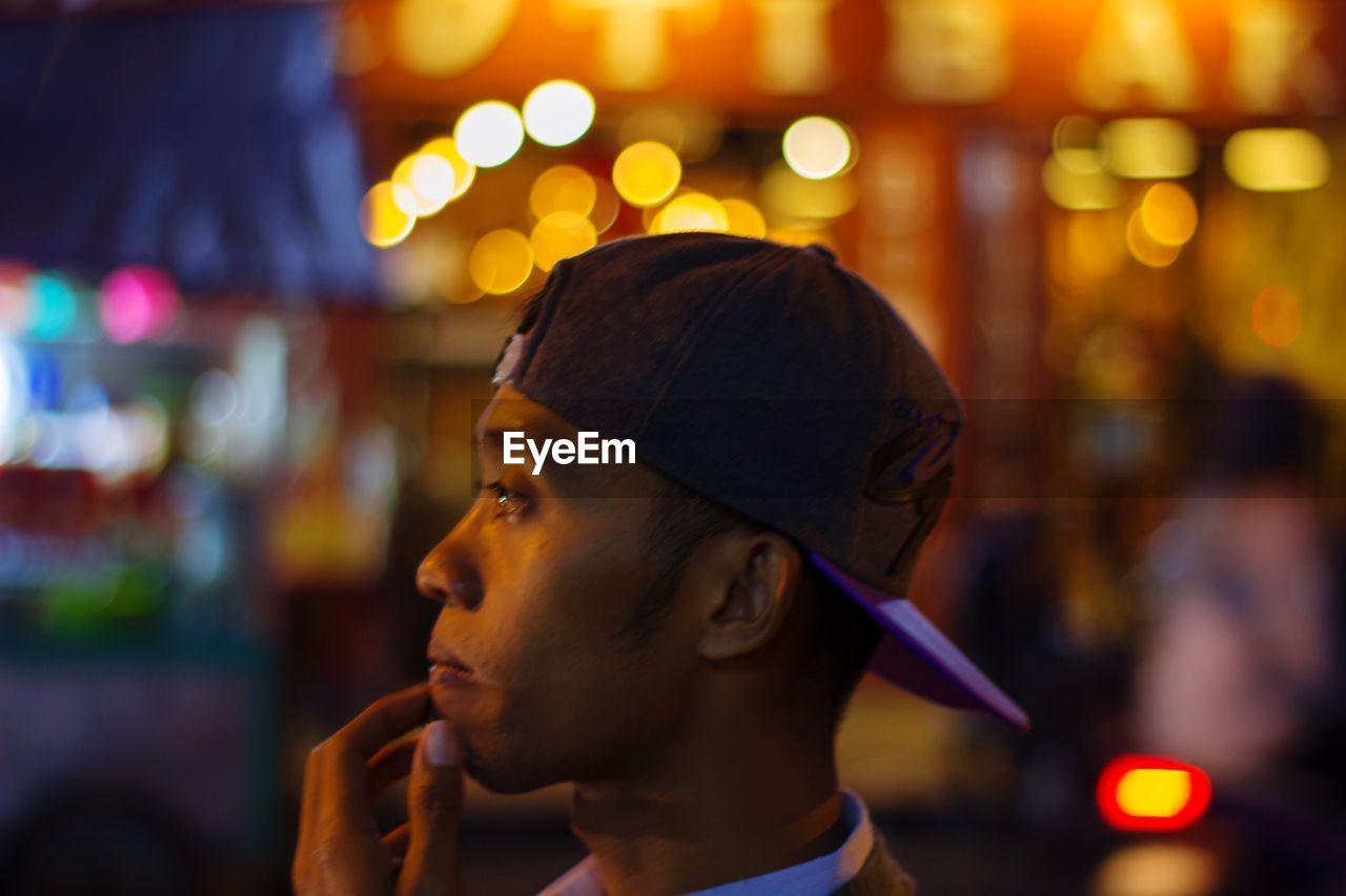 headshot, portrait, one person, focus on foreground, night, illuminated, real people, young adult, lifestyles, leisure activity, close-up, looking, incidental people, looking away, hat, side view, young men, cap, contemplation, profile view