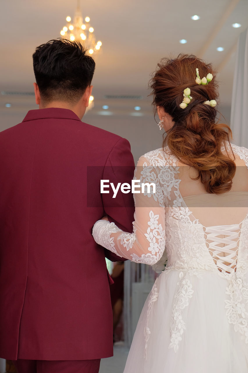 wedding, bride, two people, newlywed, wedding dress, celebration, event, togetherness, women, love, life events, adult, real people, positive emotion, rear view, couple - relationship, men, bonding, married, bridegroom, wedding ceremony