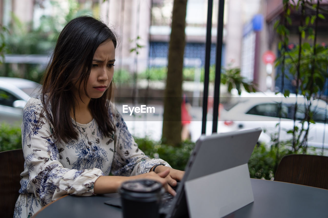 Young woman using laptop while sitting at sidewalk cafe in city