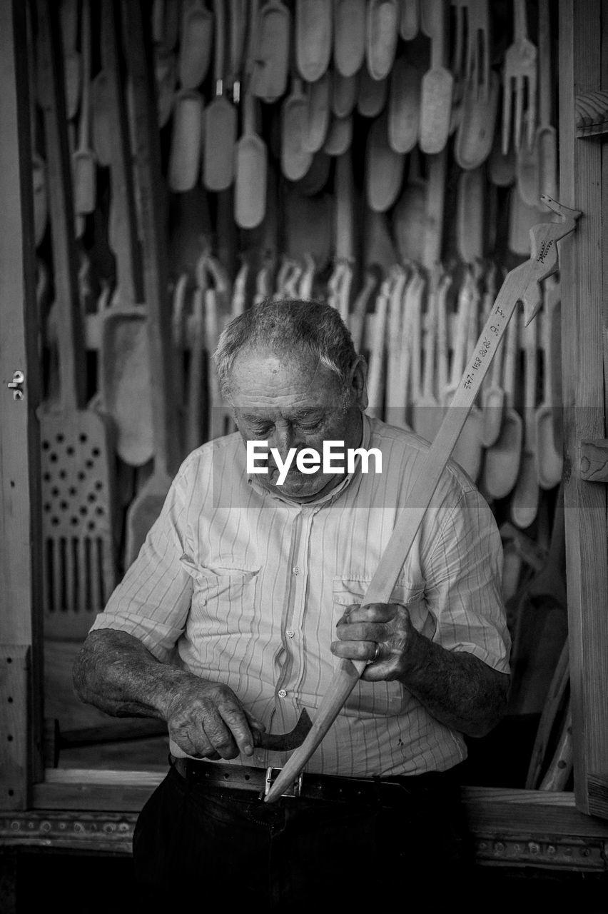 Senior man with work tools in workshop