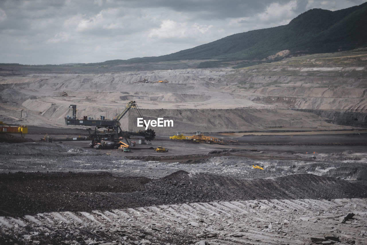 View Of Open-Pit Mine Against Cloudy Sky