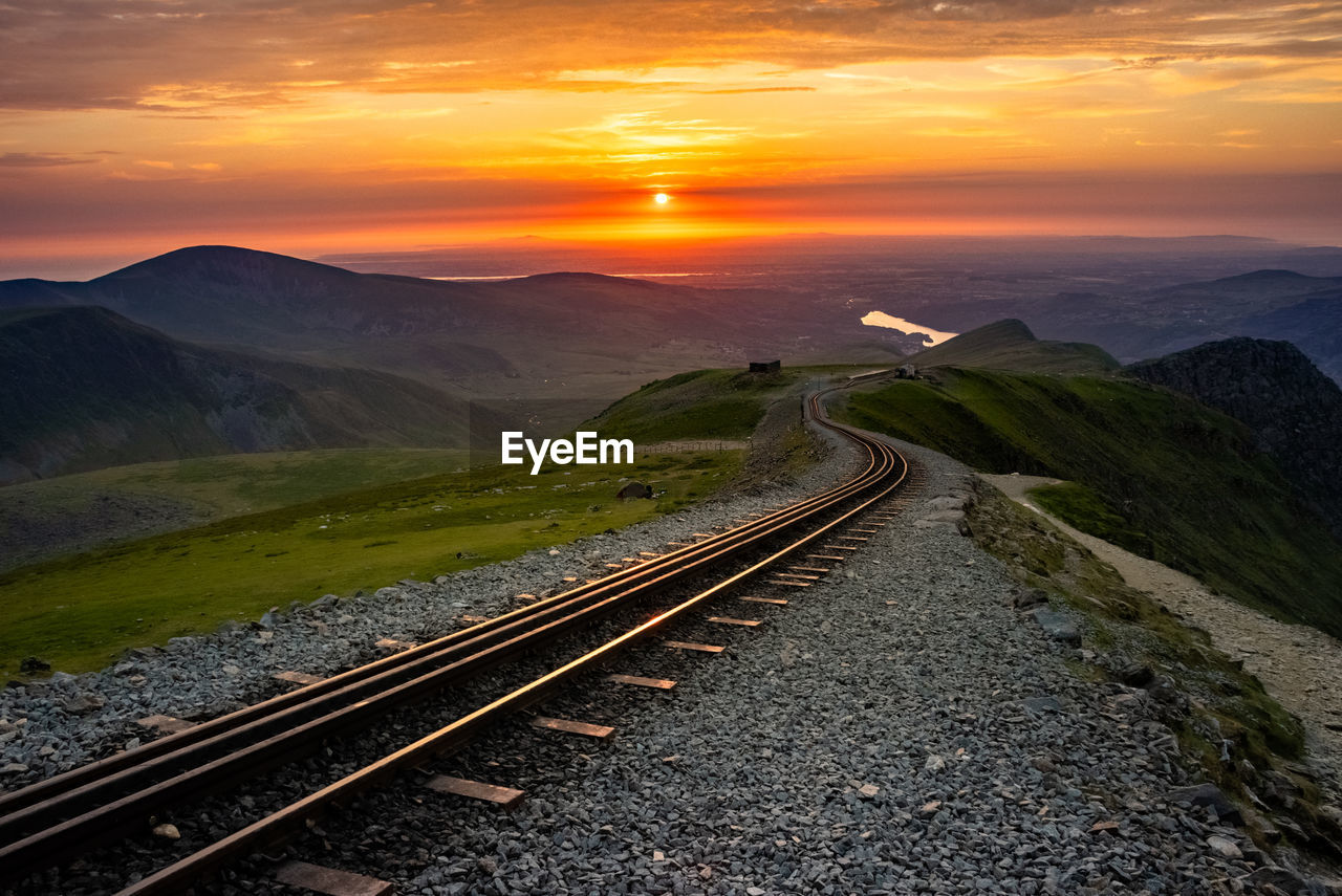 sunset, sky, transportation, beauty in nature, scenics - nature, track, nature, mountain, the way forward, cloud - sky, railroad track, direction, rail transportation, mountain range, no people, orange color, tranquil scene, tranquility, non-urban scene, landscape, diminishing perspective, long