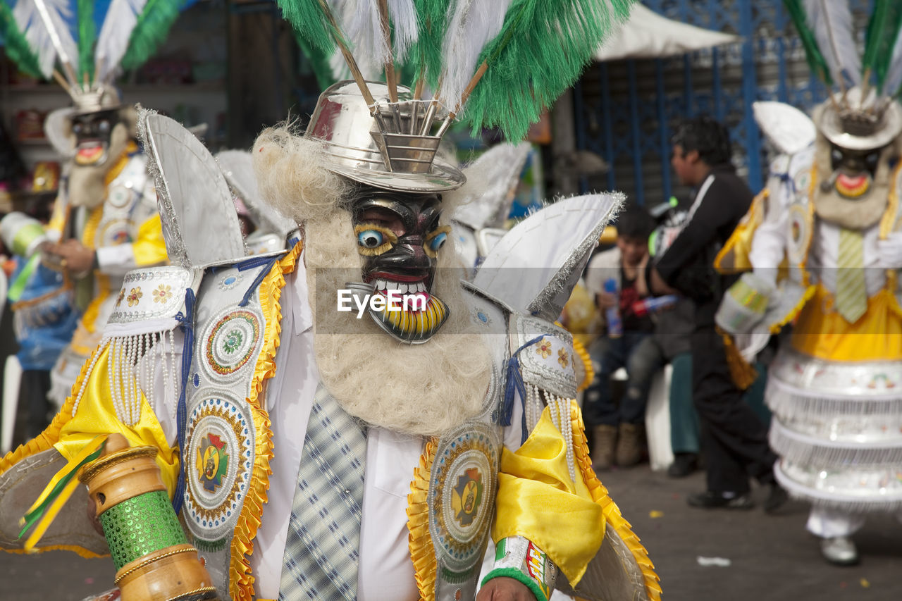 representation, arts culture and entertainment, celebration, day, real people, disguise, focus on foreground, street, costume, city, incidental people, art and craft, people, creativity, unrecognizable person, outdoors, mask, festival, carnival - celebration event, obscured face