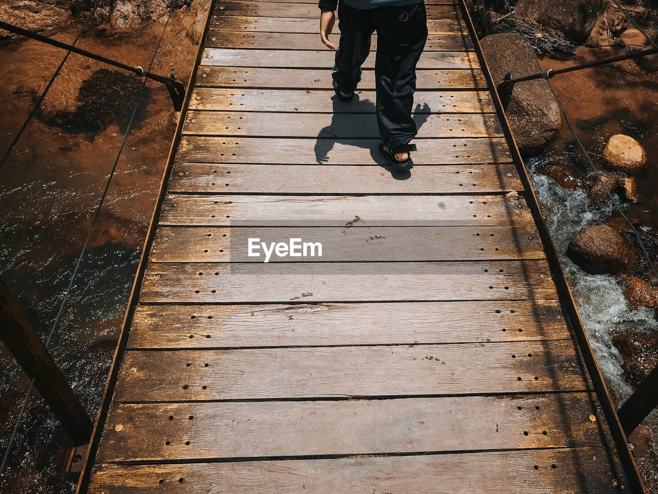 low section, human leg, real people, body part, one person, human body part, lifestyles, high angle view, standing, leisure activity, men, day, shoe, walking, nature, footpath, wood - material, outdoors, human foot, human limb