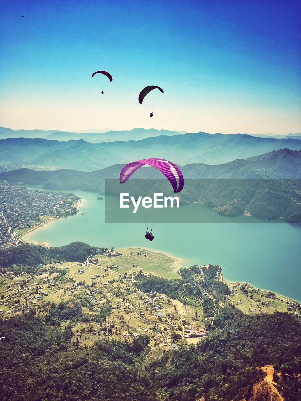 parachute, adventure, mountain, scenics, mid-air, nature, extreme sports, beauty in nature, paragliding, day, outdoors, leisure activity, clear sky, sky, real people, tranquil scene, mountain range, tranquility, landscape, flying, lifestyles, one person, water, people