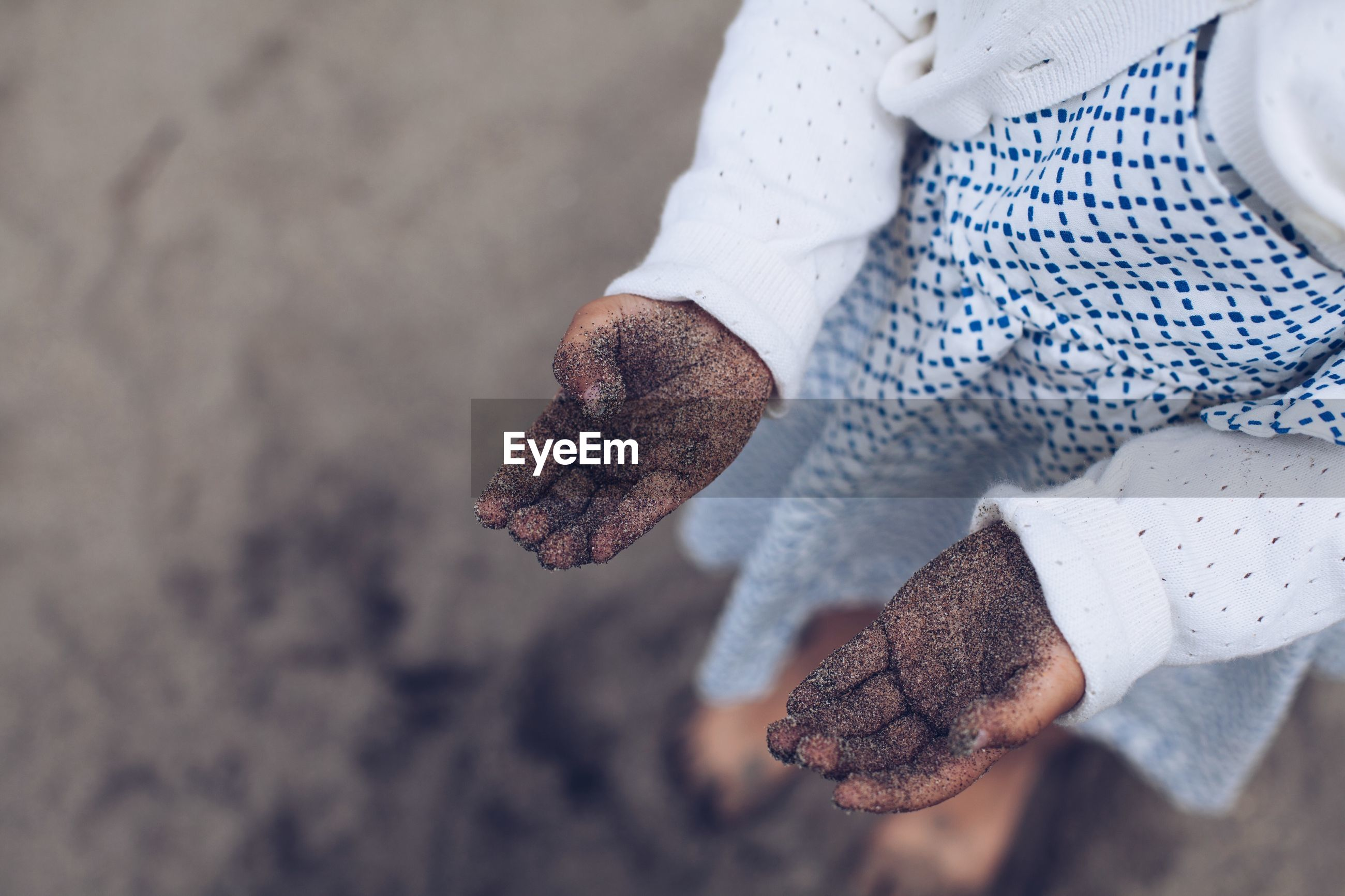 High angle view of a girls hands full of sand