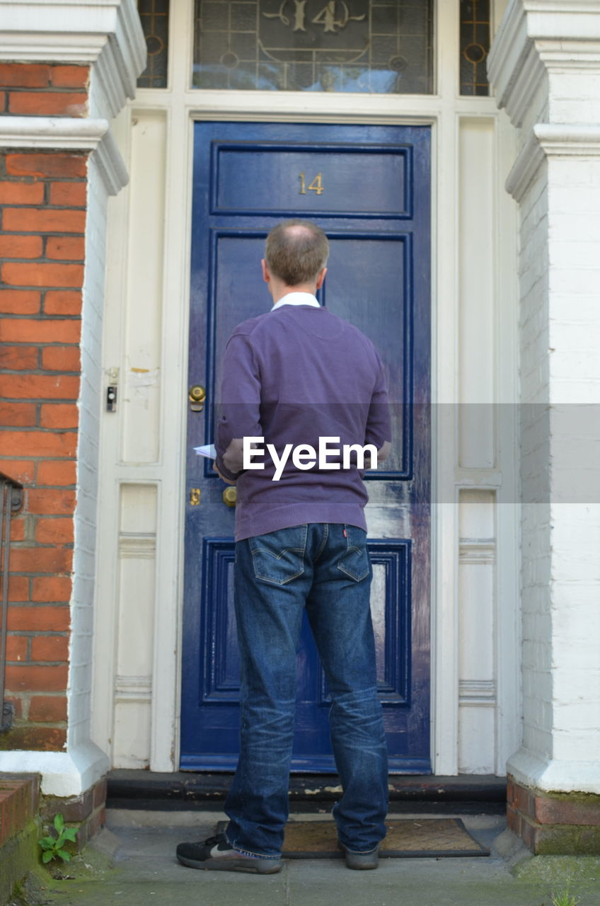 rear view, entrance, door, architecture, one person, men, building, building exterior, full length, standing, casual clothing, built structure, males, house, day, child, doorway, real people, front stoop, outdoors, leaving, waiting, contemplation