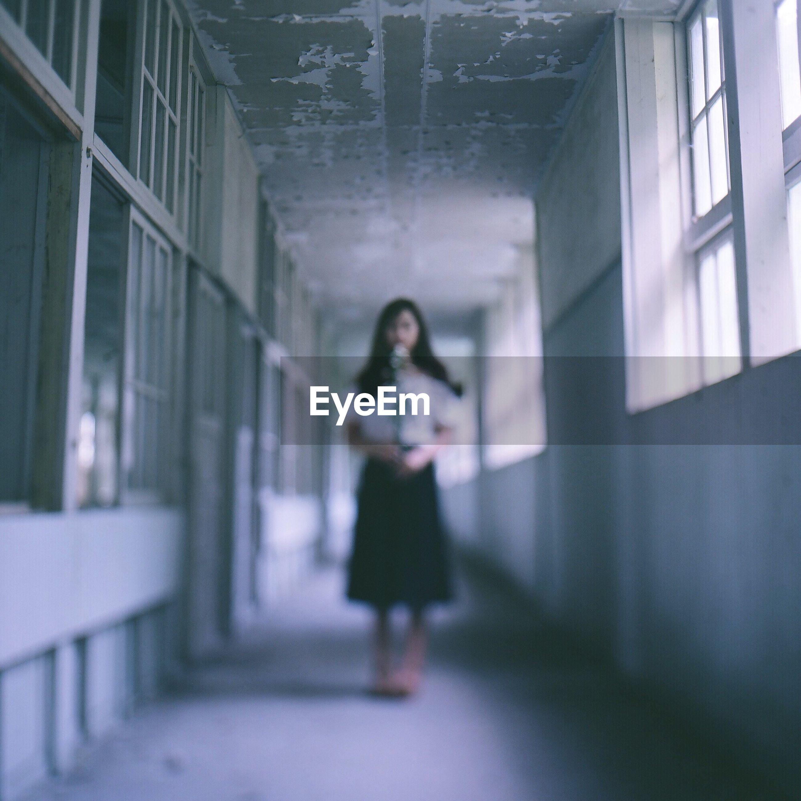 Woman Standing In Corridor Of Building