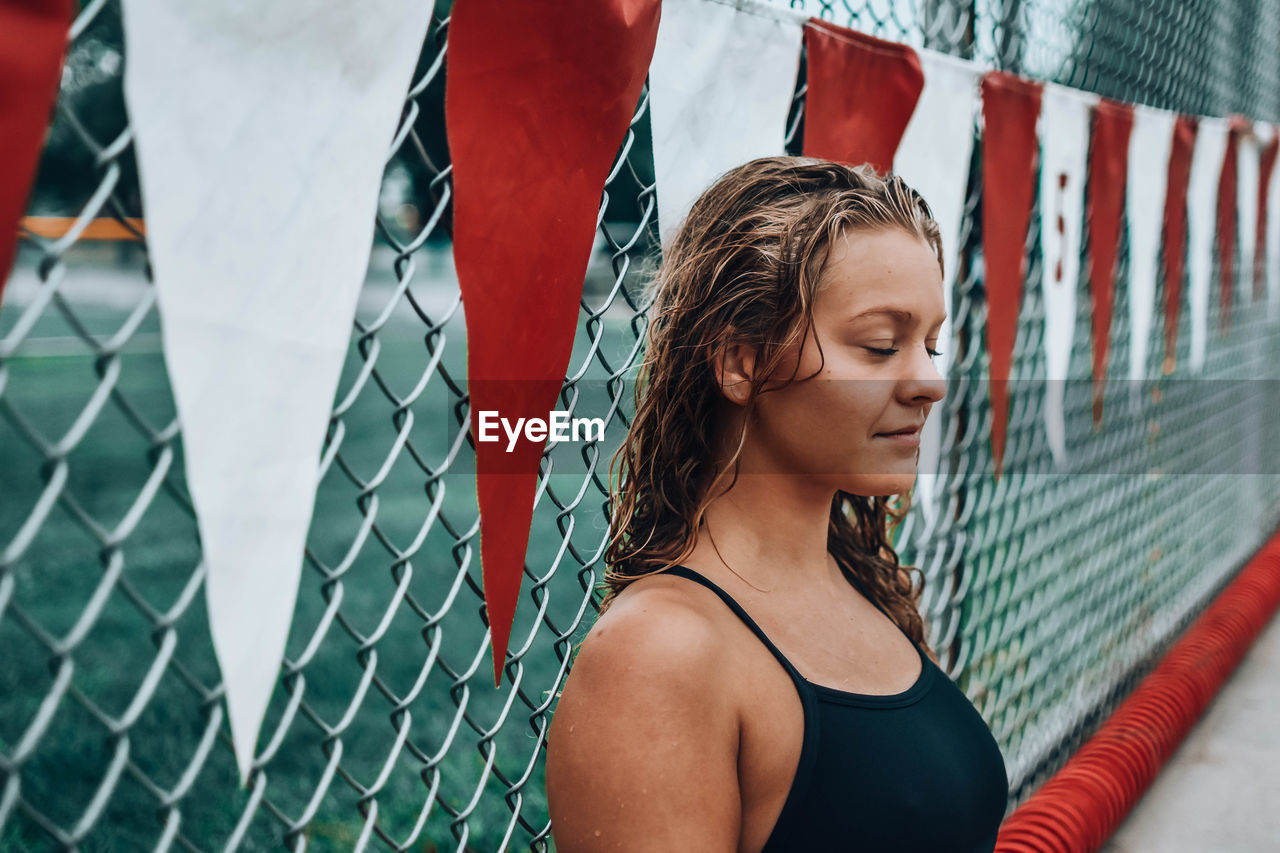 one person, real people, lifestyles, young adult, fence, young women, leisure activity, portrait, headshot, focus on foreground, looking, boundary, sport, barrier, hairstyle, chainlink fence, day, women, hair, outdoors, beautiful woman