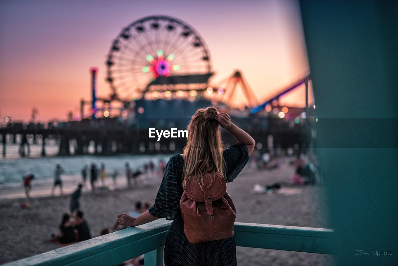 ferris wheel, leisure activity, amusement park, real people, rear view, outdoors, built structure, focus on foreground, amusement park ride, arts culture and entertainment, illuminated, travel destinations, one person, sky, lifestyles, building exterior, women, sunset, architecture, water, nature, day, close-up, young adult, people