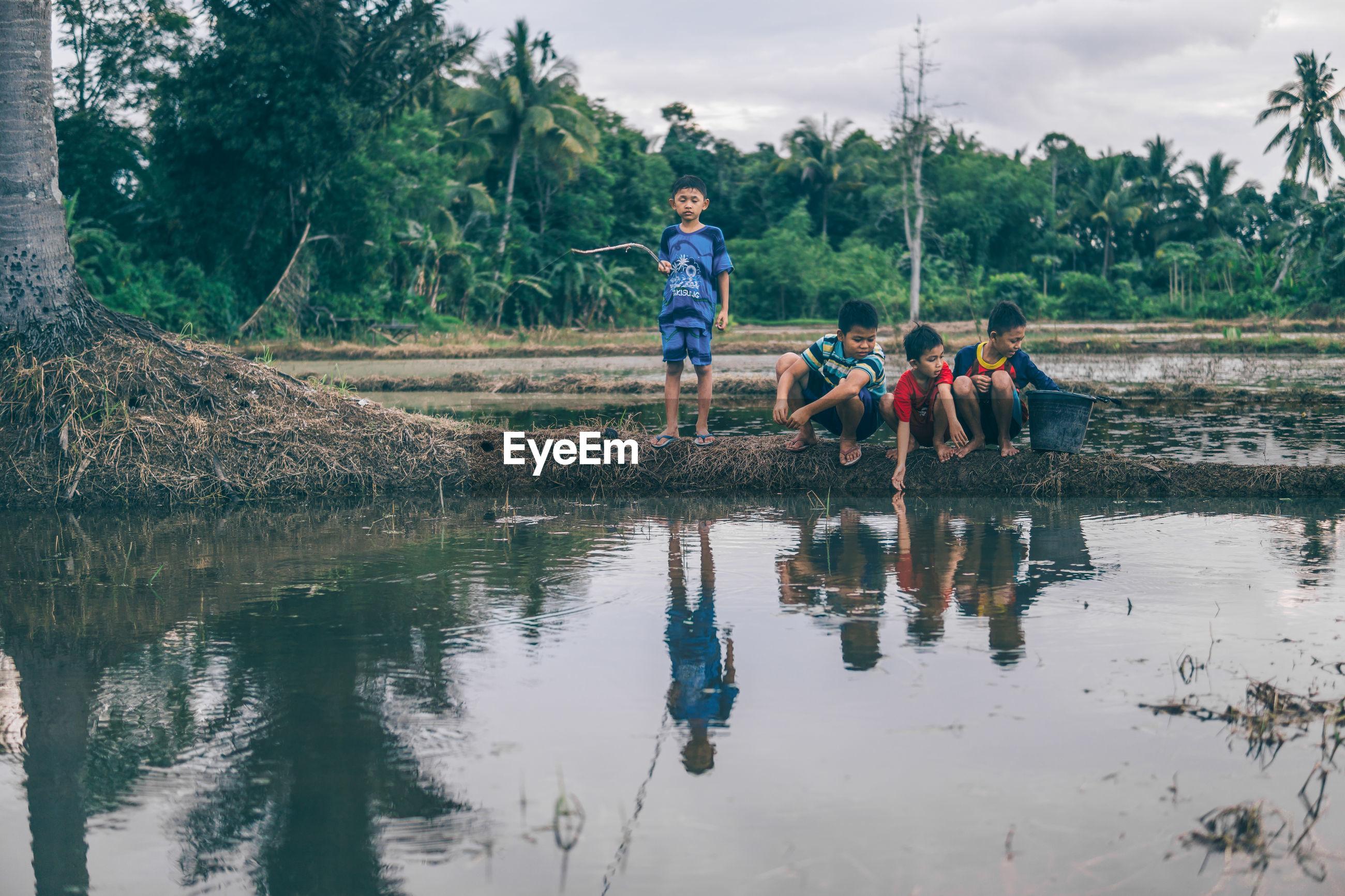 Boys sitting by wetland