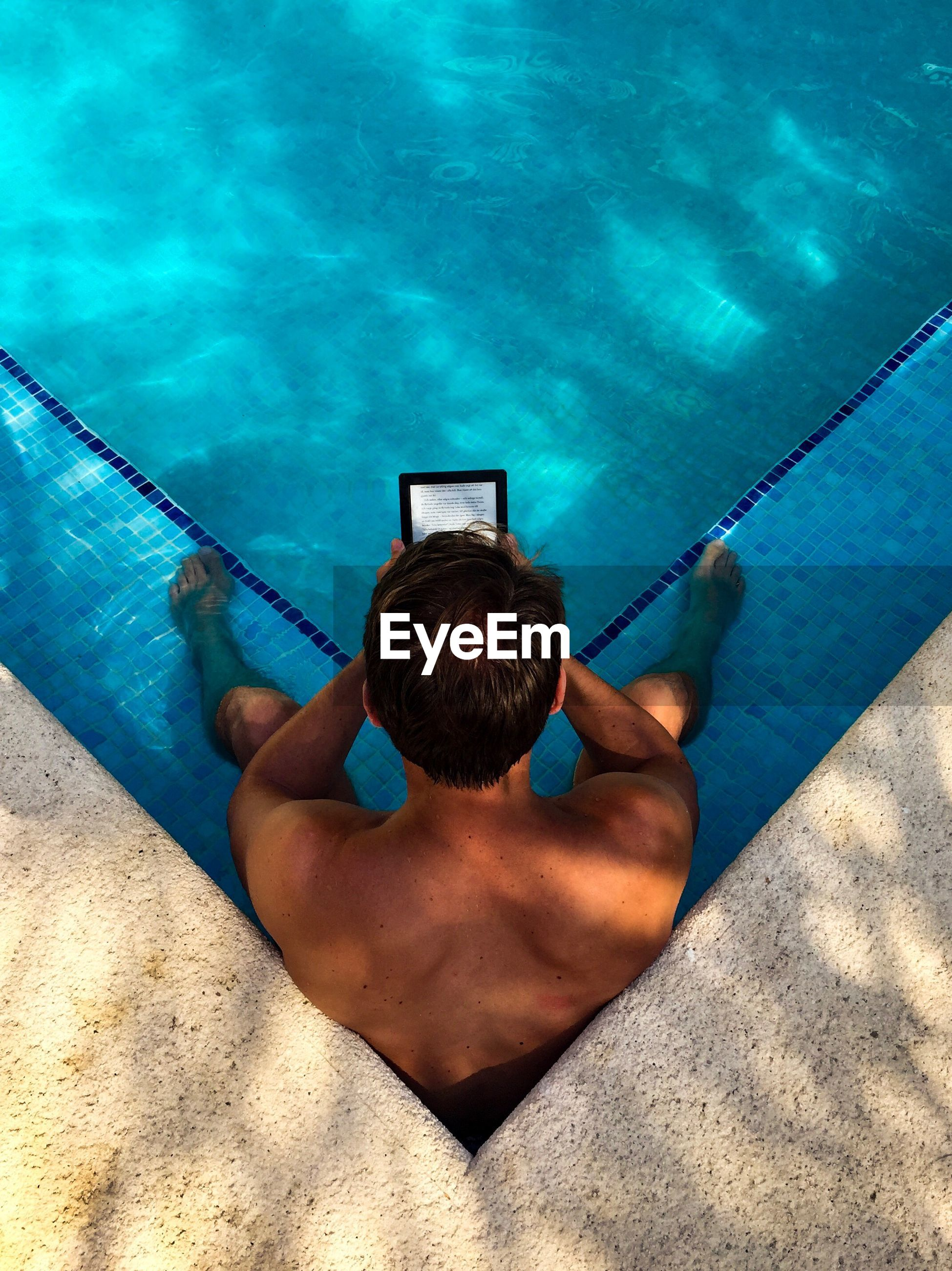 High angle view of shirtless man holding digital tablet while sitting in swimming pool