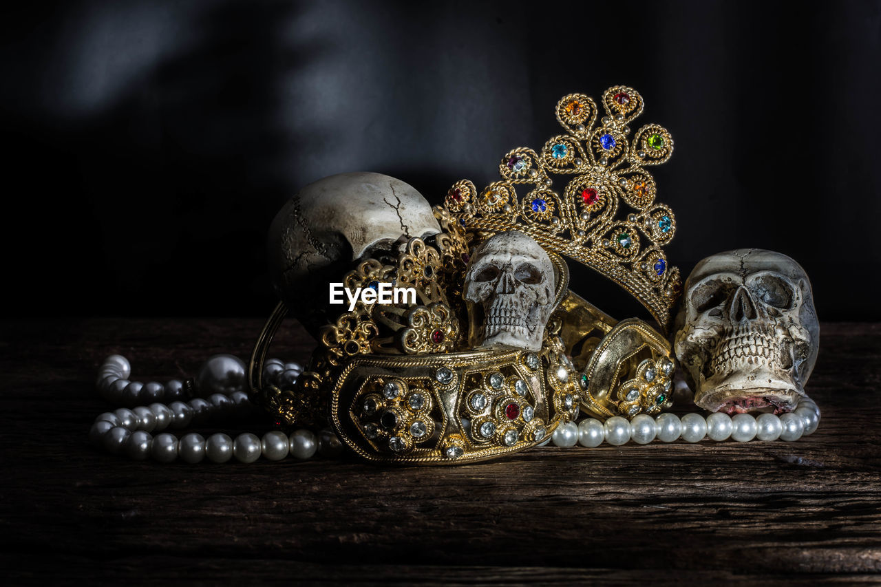Close-up of human skulls and gold jewelry on table against black background