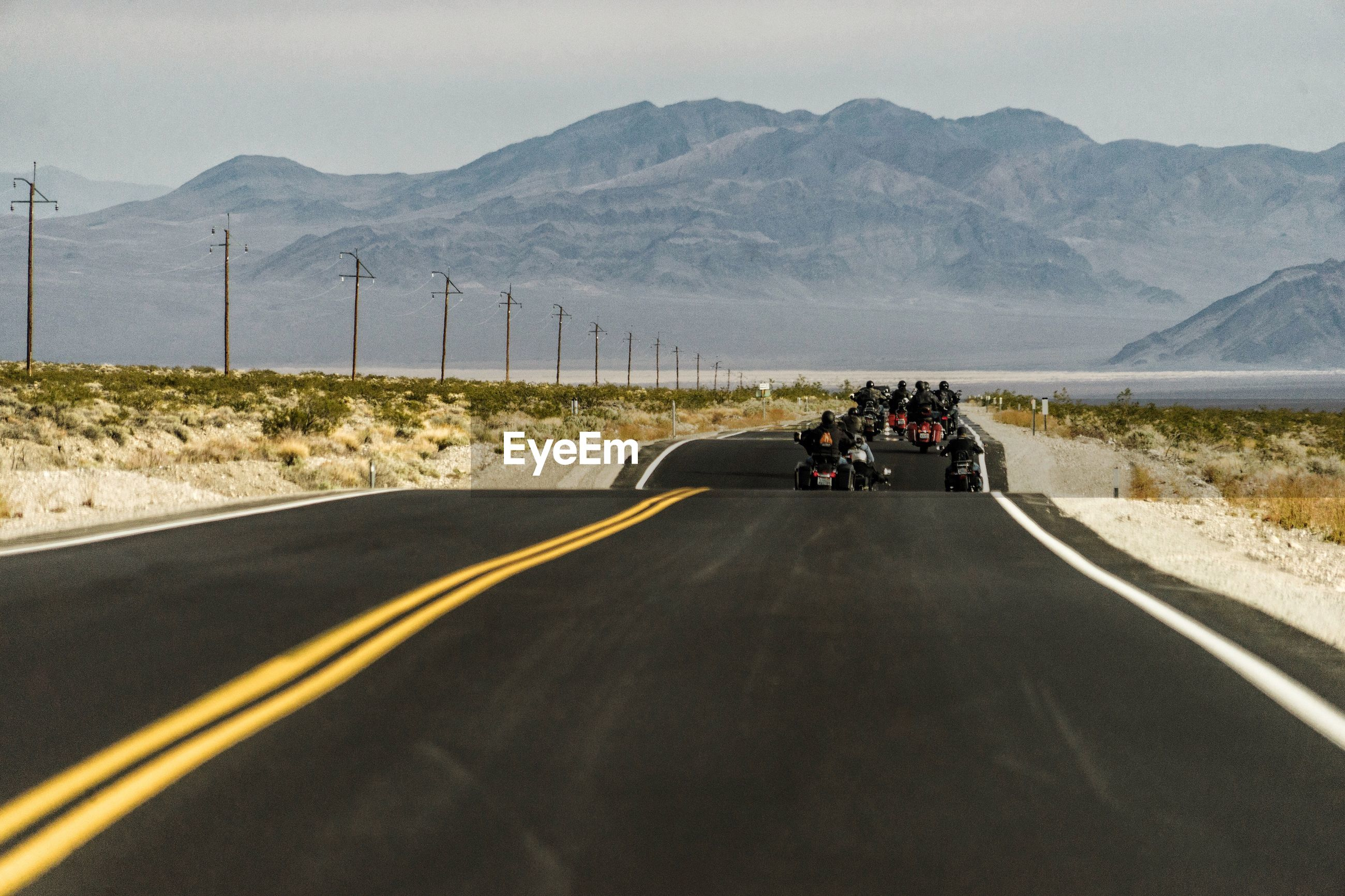 Rear view of people riding motorcycles on country road against mountains