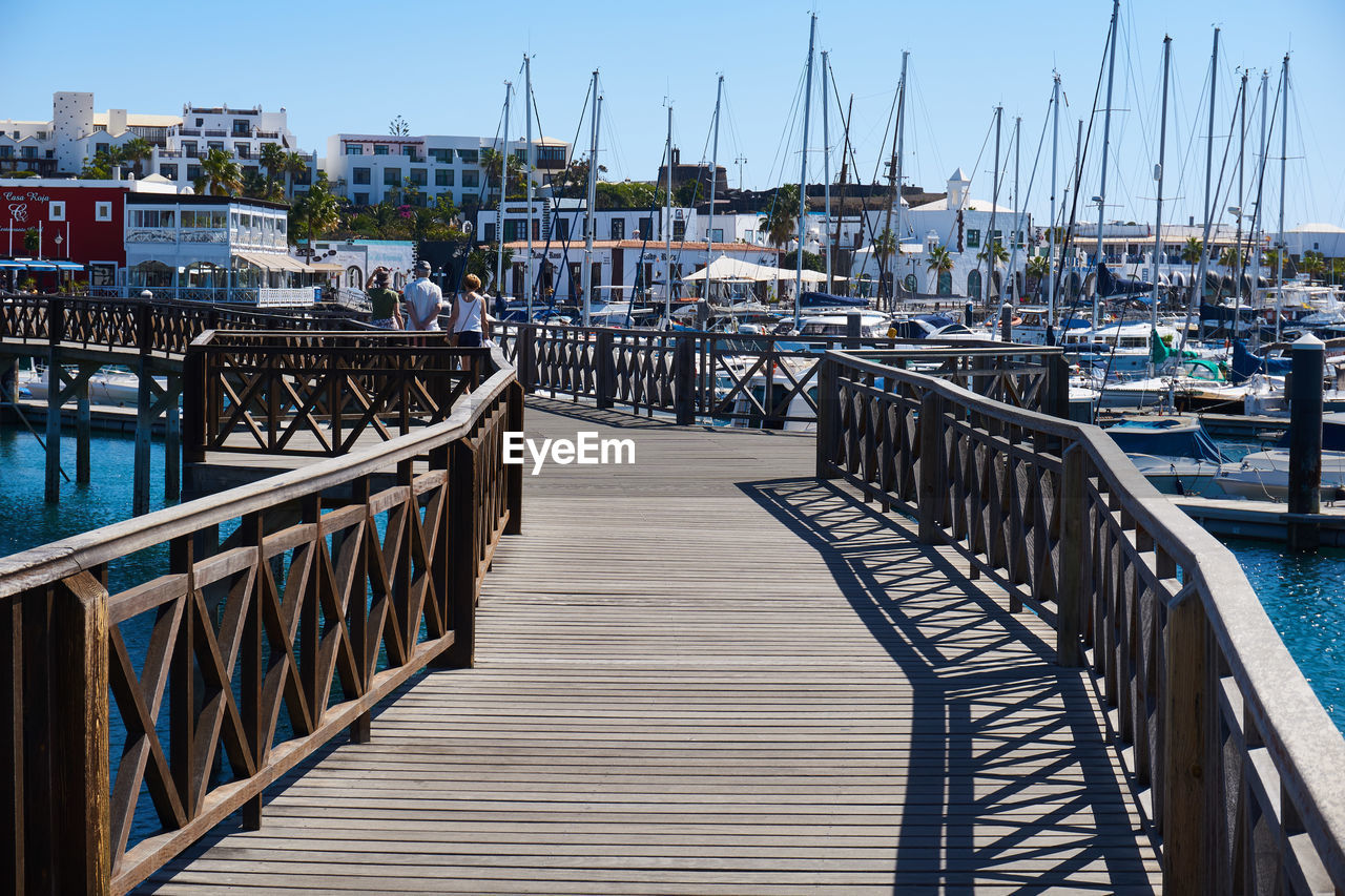 water, architecture, railing, built structure, nautical vessel, transportation, pier, sky, nature, day, mode of transportation, harbor, sea, moored, clear sky, building exterior, the way forward, wood - material, sailboat, no people, outdoors, yacht, port