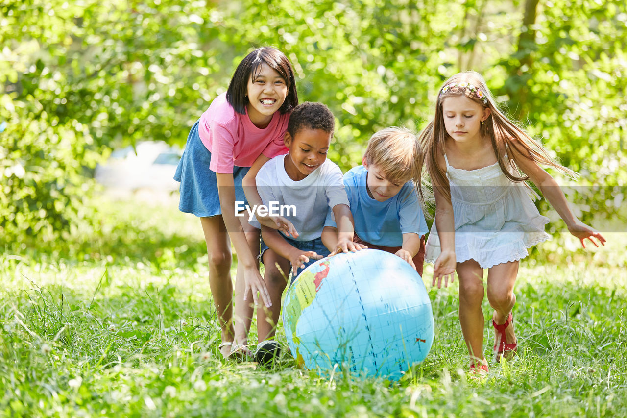 Friends playing with globe against trees
