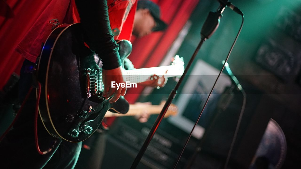 Midsection Of Man Playing Guitar On Stage