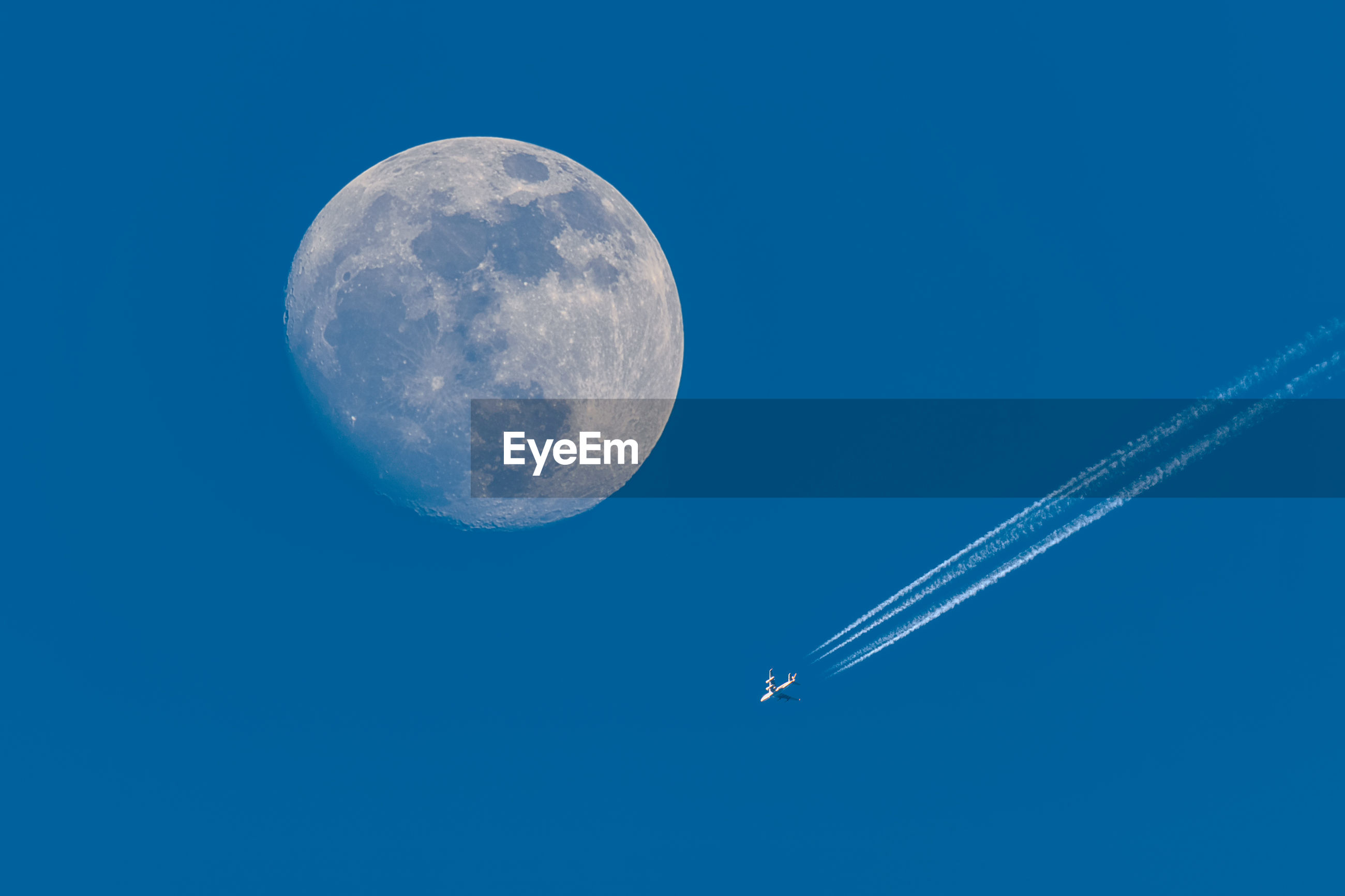 Full moon and flying plane with blue sky.
