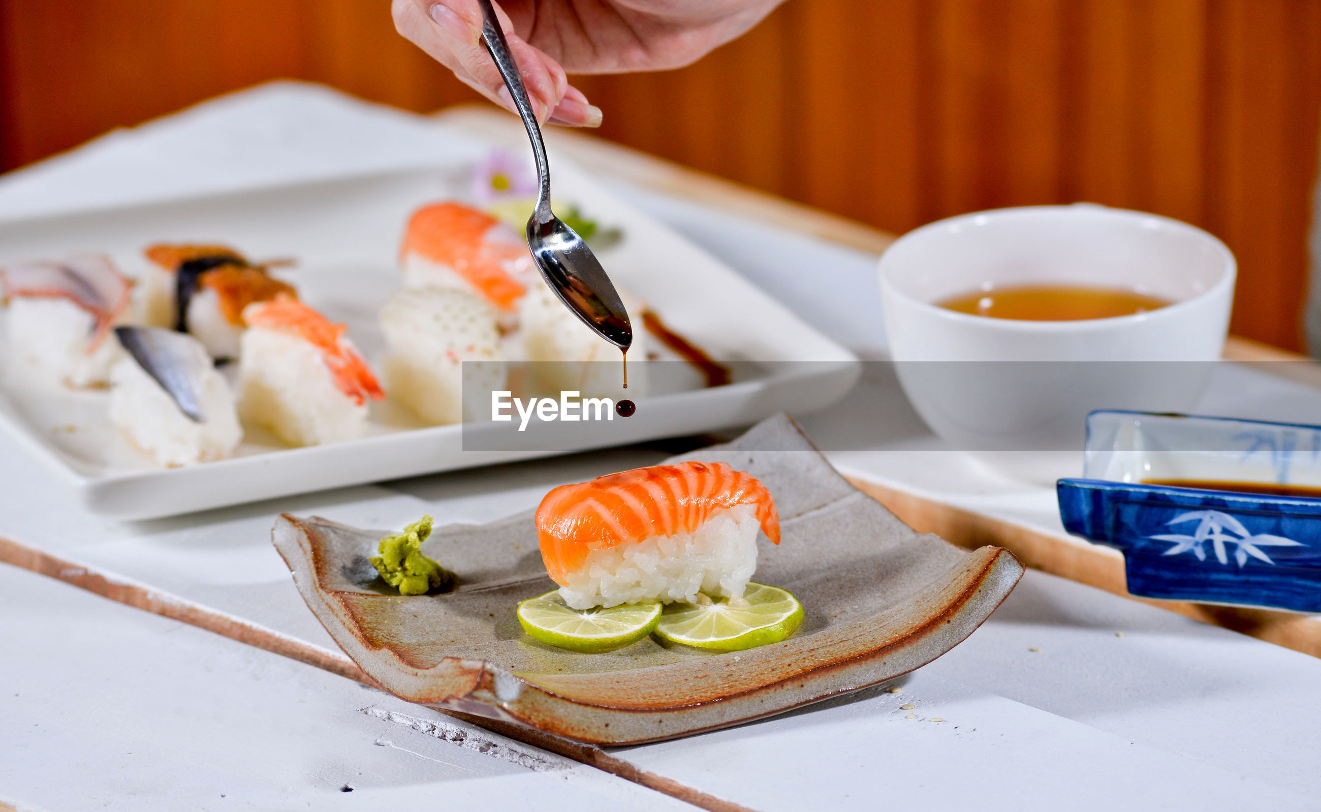 Cropped image of hand pouring sauce over sushi on table