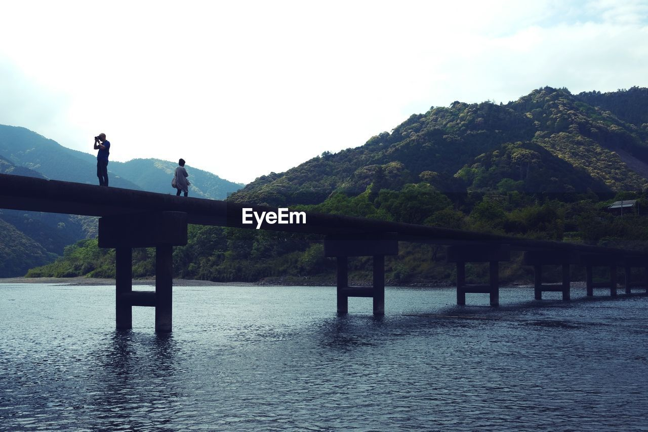 water, sky, waterfront, mountain, scenics - nature, bridge, tranquility, beauty in nature, nature, built structure, real people, connection, tranquil scene, day, bridge - man made structure, architecture, two people, non-urban scene, unrecognizable person, outdoors
