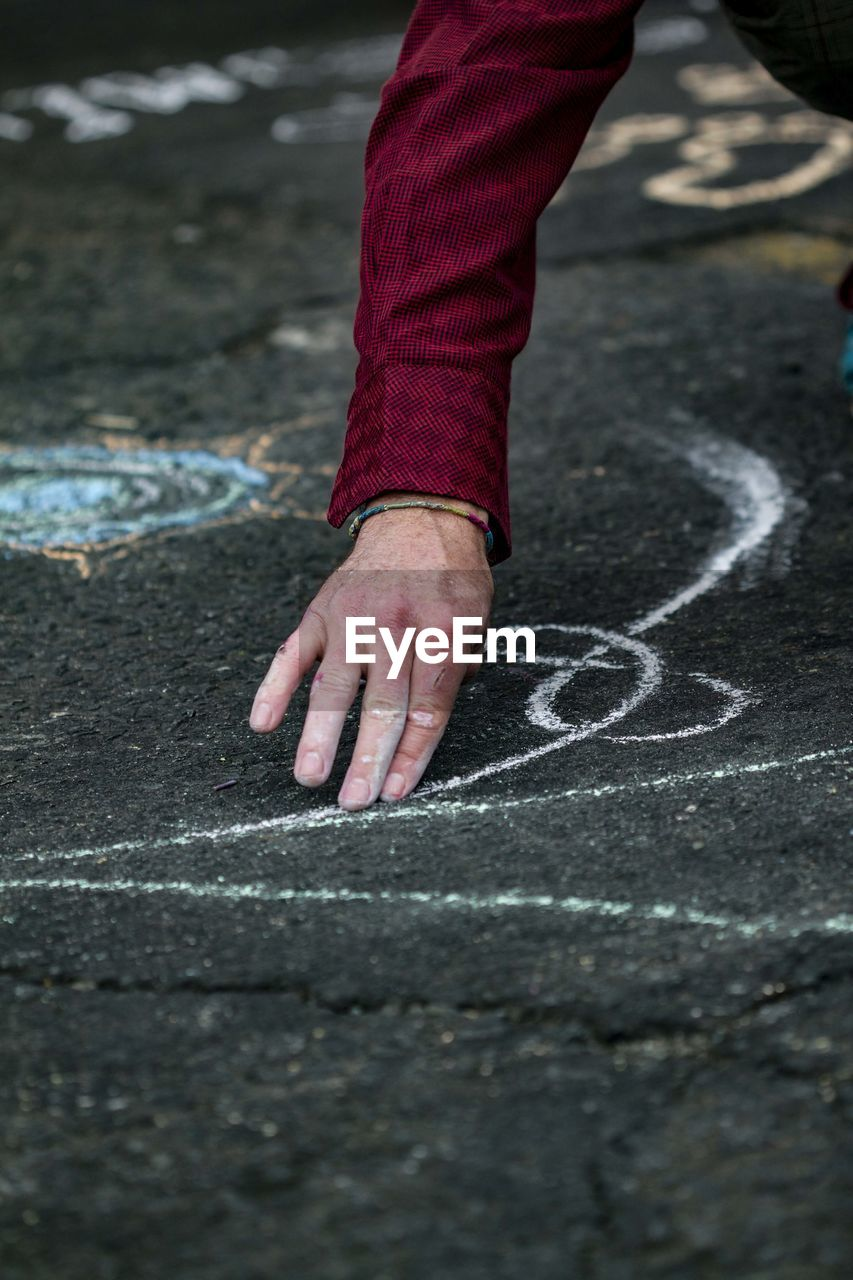 Cropped hand of man chalk drawing on road