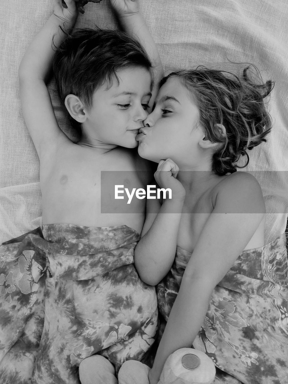 Siblings Kissing While Lying On Bed