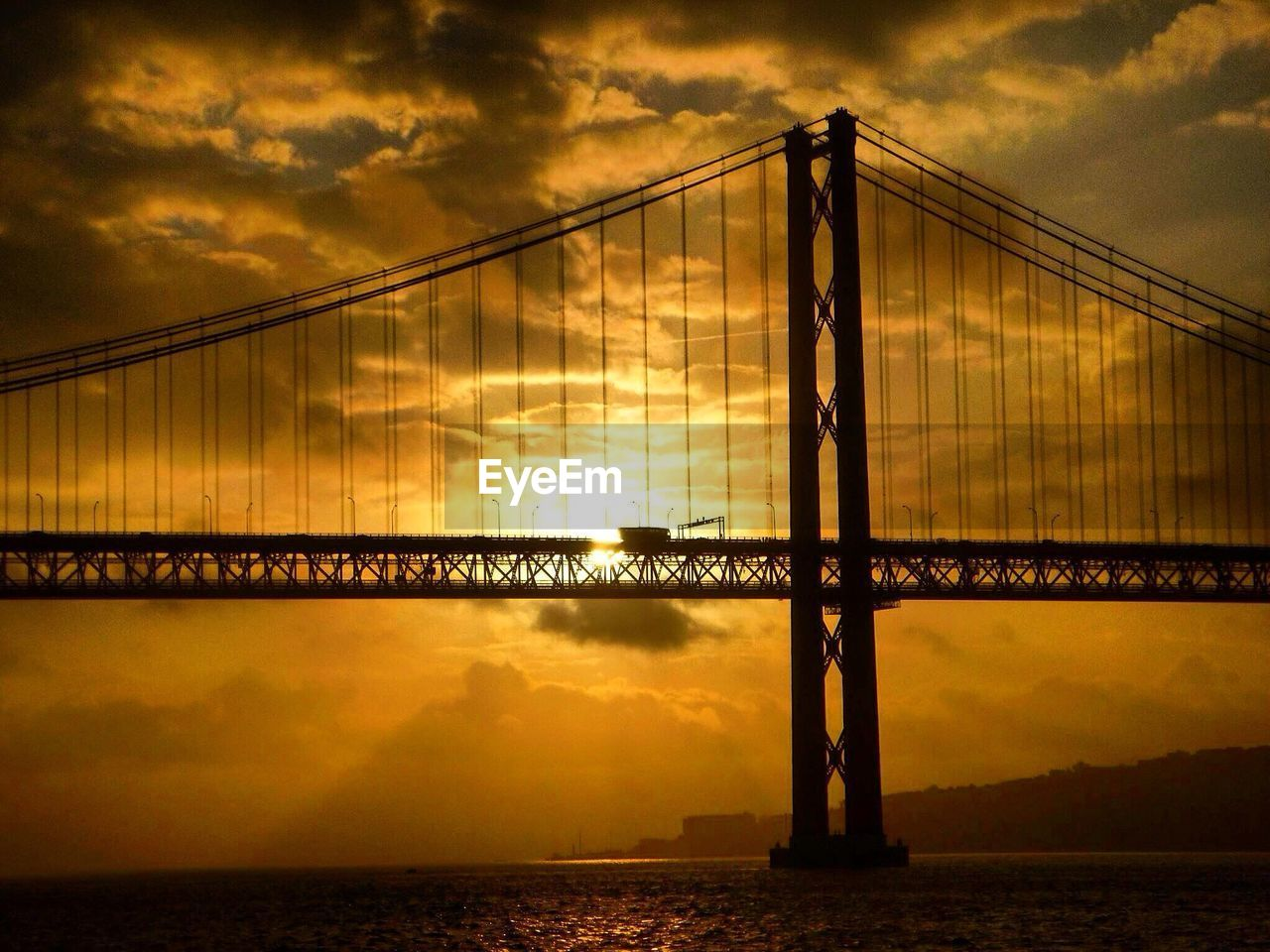 bridge - man made structure, sky, suspension bridge, connection, engineering, architecture, water, sunset, built structure, cloud - sky, river, transportation, outdoors, bridge, travel destinations, nature, no people, beauty in nature, illuminated, city, day