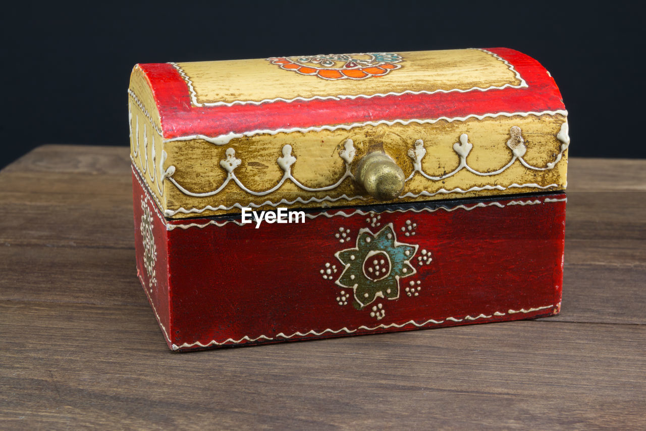 indoors, still life, red, table, close-up, no people, single object, art and craft, wood - material, focus on foreground, wealth, craft, antique, studio shot, old, carving - craft product, gold colored, luxury, box, black background, floral pattern