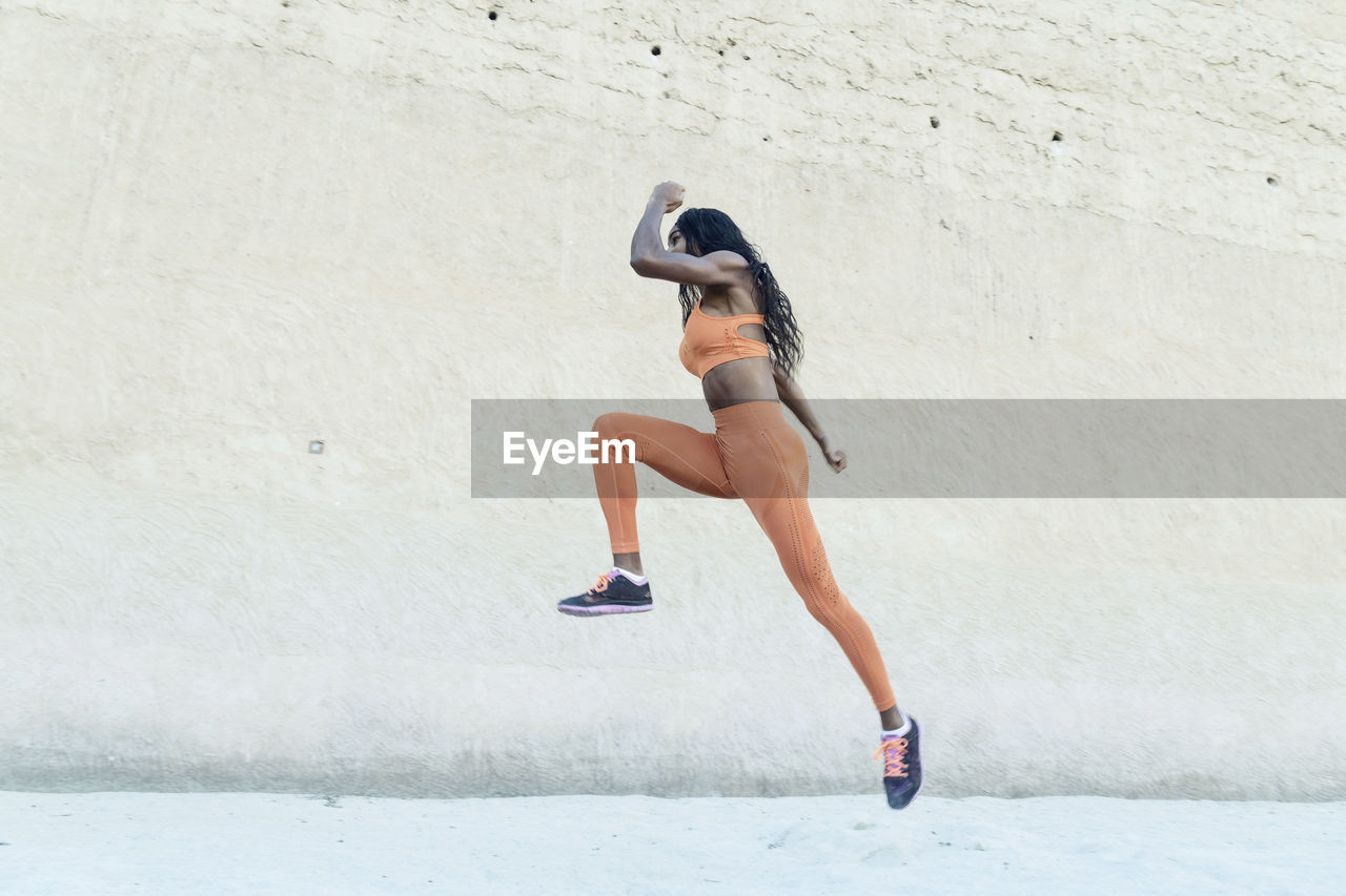 Side view of woman running on wall