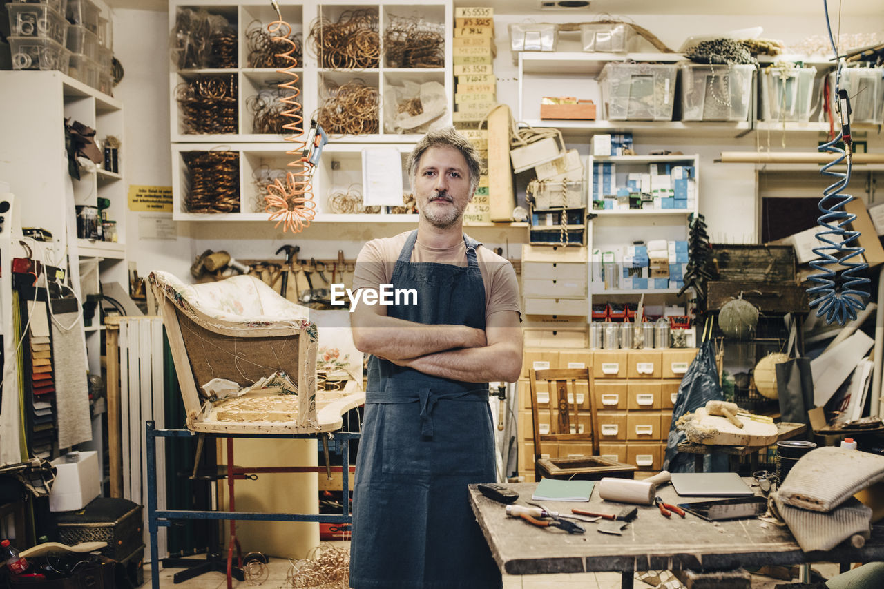 small business, one person, standing, occupation, retail, store, front view, looking at camera, business, portrait, casual clothing, arms crossed, young adult, young men, indoors, shelf, workshop, men, real people, entrepreneur